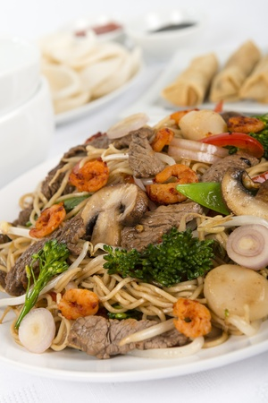 Chow Mein - Chinese Stir-fried noodles with beef, shrimp and vegetables served with sring rolls, prawn crackers and dipping sauce on a white background  photo