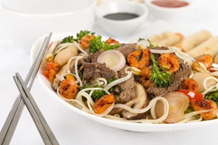 Chow Mein - Chinese Stir-fried noodles with beef, shrimp and vegetables on a white background  photo