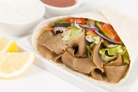Donner Kebab Wrap - Donner de la viande avec salade envelopp� dans un pain plat servi avec du yogourt � la menthe et raita, sauce chili et des quartiers de citron sur un fond blanc Gros plan
