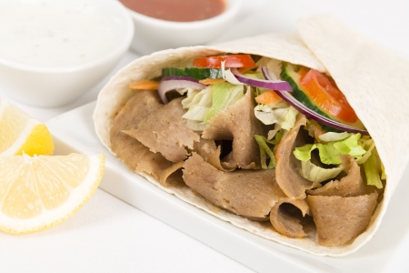 Donner Kebab Wrap - Donner meat with salad wrapped in a flatbread served with mint and yogurt raita, chili sauce and lemon wedges on a white background  Close up