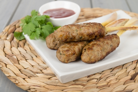 Nem Noung Xa - Vietnamese minced pork sausages on lemongrass skewers served with chili sauce  Stock Photo - 17050382