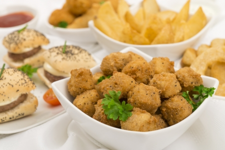 nibbles: Party Food - Breaded Mushrooms, mini cheeseburgers and onion rings with chili sauce and sour cream and chives dip  Stock Photo