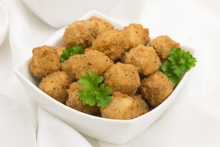 Fried Popcorn Chicken - Battered deep fried chicken balls on a white background