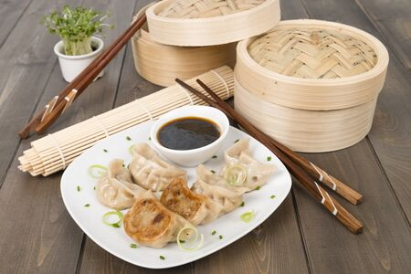 Yaki-Gyoza - Japanese pan-fried dumplings served with a soy based dipping sauce  Dark wood background  Stock Photo