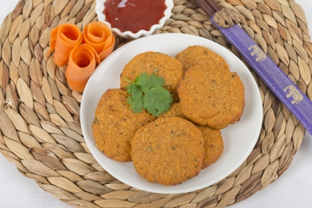 pla: Tod Man Pla - Thai fried fishcakes served with a bowl of sweet chili sauce and garnished with coriander leaves  Stock Photo