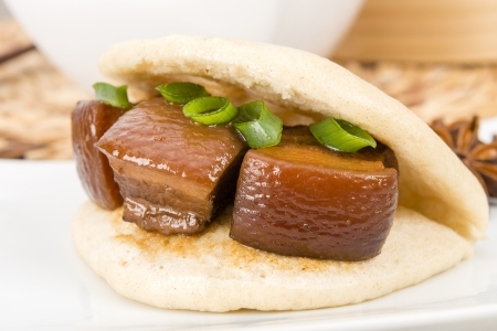 rou: Hong Shao Rou  Red Cooked Pork  - Pork belly caramelized and braised in soy sauce with star anise, cinnamon inside a steamed bun  he ye bao   Stock Photo