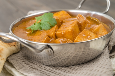 Paneer Makhani or Shahi Paneer  Paneer Butter Masala  - Indian curd cheese curry in a balti dish, served with naan bread and garnished with coriander leaves  Stock Photo