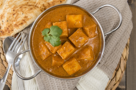 curd: Paneer Makhani or Shahi Paneer  Paneer Butter Masala  - Indian curd cheese curry in a balti dish, served with naan bread and garnished with coriander leaves  Stock Photo
