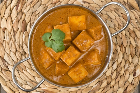 Paneer Makhani or Shahi Paneer  Paneer Butter Masala  - Indian curd cheese curry in a balti dish, served with naan bread and garnished with coriander leaves  photo