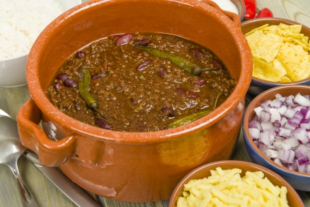 Chili con Carne - Spicy minced beef stew with chilies  Sides or diced onions, grated cheese,  white rice, sour cream and corn chips  photo