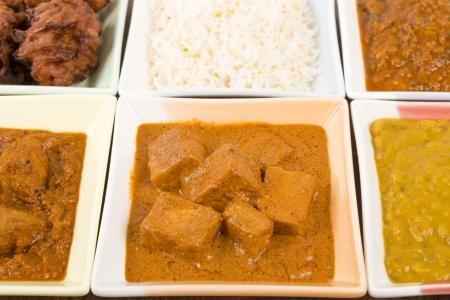 Thali - Indian meal set with vegetarian and meat curries, pilau rice and onion bhajis - tarka dal, paneer makhani, pork vindaloo and keema madras  photo