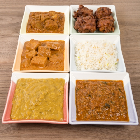 indian meal: Thali - Indian meal set with vegetarian and meat curries, pilau rice and onion bhajis - tarka dal, paneer makhani, pork vindaloo and keema madras  Stock Photo