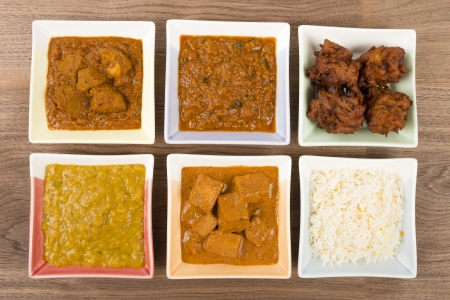 Thali - Indian meal set with vegetarian and meat curries, pilau rice and onion bhajis - tarka dal, paneer makhani, pork vindaloo and keema madras  Stock Photo