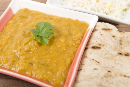 Tarka Dal - Indian yellow split pea curry garnished with coriander and served with pilau rice and chapatis Close up