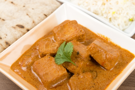 Paneer Makhani or Shahi Paneer  Paneer Butter Masala  - Indian curd cheese curry served garnished with coriander leaves and served with pilau rice and chapatis  Stock Photo