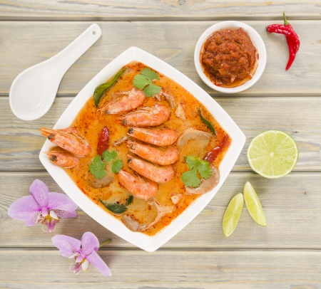 Tom Yum Nam Khon - Creamy Thai soup with prawns and mushrooms garnished with coriander and served with lime wedges  Close up