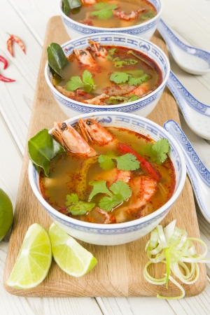 Tom Yum Goong - Thai hot and sour soup with king prawns and oyster mushrooms served with lime wedges Stock Photo - 18036228