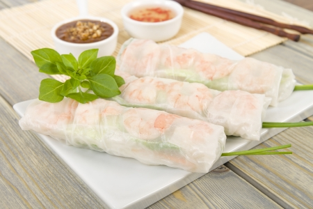 Goi Cuon - Vietnamese fresh summer rolls filled with prawns, pork, herbs, rice vermicelli and vegetables  Served with hoisin and peanut sauce dip and nuoc mam cham  Wooden background Stock Photo - 18036232