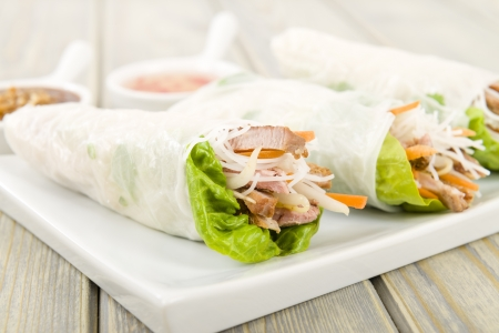 goi: Goi Cuon - Vietnamese fresh summer rolls filled with prawns, pork, herbs, rice vermicelli and vegetables  Served with hoisin and peanut sauce dip and nuoc mam cham  Wooden background Stock Photo