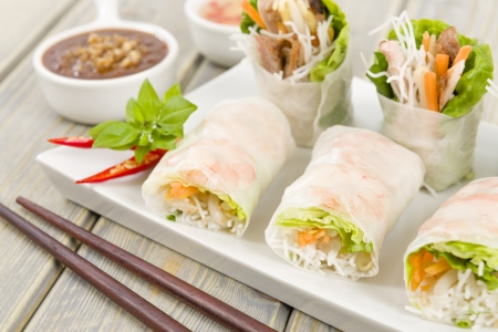 Goi Cuon - Vietnamese fresh summer rolls filled with prawns, pork, herbs, rice vermicelli and vegetables  Served with hoisin and peanut sauce dip and nuoc mam cham  Wooden background Stock Photo