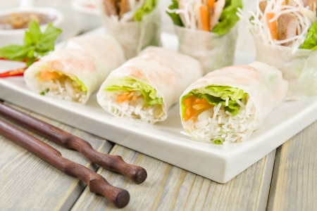 Goi Cuon - Vietnamese fresh summer rolls filled with prawns, pork, herbs, rice vermicelli and vegetables  Served with hoisin and peanut sauce dip and nuoc mam cham  Wooden background Stock Photo - 18036236