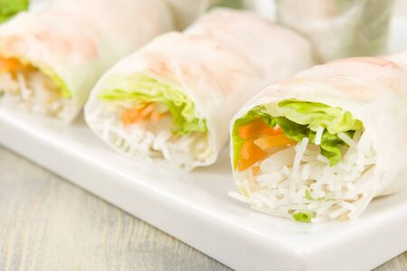 hoisin: Goi Cuon - Vietnamese fresh summer rolls filled with prawns, pork, herbs, rice vermicelli and vegetables  Served with hoisin and peanut sauce dip and nuoc mam cham  Wooden background Stock Photo
