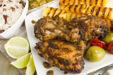 Jerk Chicken - Jamaican marinated BBQ chicken served with grilled pineapple, rice and peas and lime wedges