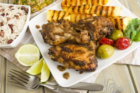 Jerk Chicken - Jamaican marinated BBQ chicken served with grilled pineapple, rice and peas and lime wedges   photo
