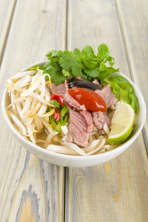 hoisin: Pho Bo - Vietnamese fresh rice noodle soup with beef, herbs and chili topped with hoisin and chill sauce  Vietnam s national dish