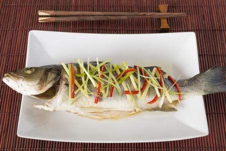pesce cotto: Pesce al vapore - stile cinese al vapore il branzino guarnito con zenzero, peperoncino e cipollotti