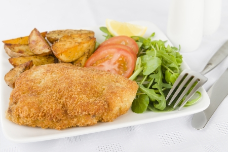 Wiener Schnitzel - Veal steak breaded and fried in butter served with salad, potato wedges and a lemon slice   photo