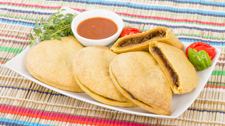 jamaican: Caribbean Jerk Beef Patty - Jamaican spicy minced jerk beef with onions and peppers in short crust pastry and scotch bonnet chillies Stock Photo