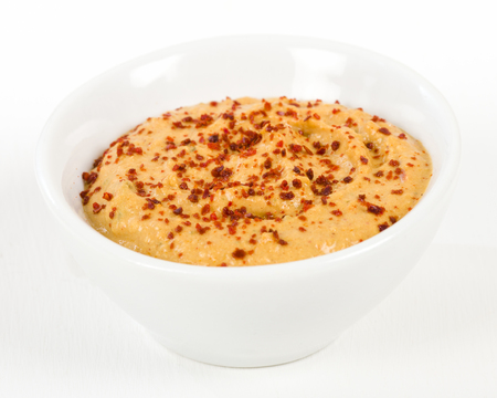 pepper flakes: Roasted Pepper Hummus in a white bowl. Stock Photo
