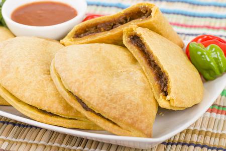 Beef Jerk Caribe Patty - Jamaica carne picante imbécil picada con cebolla y pimientos en pasta quebrada servido con salsa picante y chiles escocesa del capó. Foto de archivo