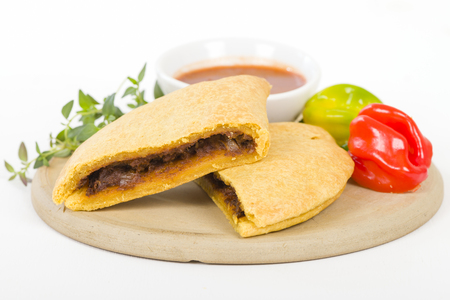 latin food: Caribbean Jerk Beef Patty - Jamaican spicy minced jerk beef with onions and peppers in short crust pastry served with spicy sauce and scotch bonnet chillies.