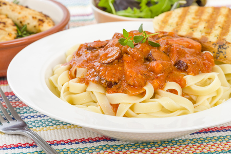white sausage: Szekely Gulyas - Hungarian goulash with pork sausage and sour cream on top of pasta and served with a slice of crusty bread. Stock Photo
