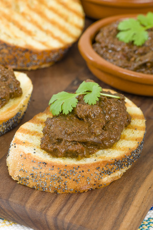 coulorful: Higados de Pollo - Chicken livers with chorizo  spring onions finished with a dark Cajun tomato sauce on top of crusty bread. Stock Photo