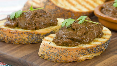 cazuela: Higados de Pollo - Chicken livers with chorizo  spring onions finished with a dark Cajun tomato sauce on top of crusty bread. Stock Photo