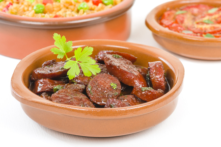 vino: Chorizo al Vino Spicy sausage cooked in red wine. Traditional Spanish tapas dish. Other tapas dishes on background.
