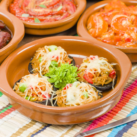 cazuela: Stuffed Mushrooms - Mushrooms topped with cooked spicy rice and cheese. Surrounded by other tapas dishes.
