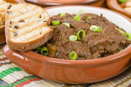 coulorful: Higados de Pollo - Chicken livers with chorizo  spring onions finished with a dark Cajun tomato sauce served with crusty bread.