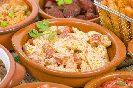 chorizo: Chicken  Chorizo - Chicken and chorizo cooked in a paprika cream sauce. Surrounded by other tapas dishes. Stock Photo