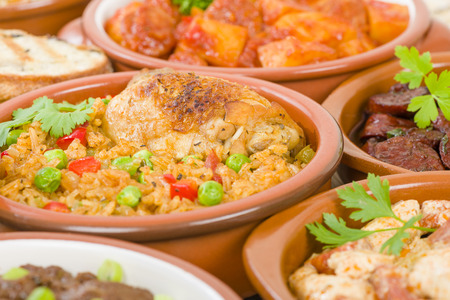 cazuela: Arroz Con Pollo - Chicken and rice cooked with sofrito and beer. Surrounded by other tapas dishes.