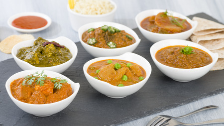 Vegetarian Curries - Selection of South Asian vegetarian curries in white bowls. Paneer Makhani, Palak Paneer, Aloo Matar, Baigan Bharta, Chilli Potatoes and Bhindi Masala. Stock Photo - 49876598