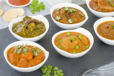 paneer: Paneer Makhani - Indian cheese cooked in a creamy sauce. Rice and other vegetarian curries on background. Stock Photo