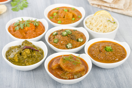 food dish: Vegetarian Curries - Selection of South Asian vegetarian curries in white bowls. Paneer Makhani, Palak Paneer, Aloo Matar, Baigan Bharta, Chilli Potatoes and Bhindi Masala, Pilau Rice and Chapattis.