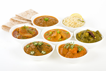 asian food: Vegetarian Curries - Selection of South Asian vegetarian curries in white bowls. Paneer Makhani, Palak Paneer, Aloo Matar, Baigan Bharta, Chilli Potatoes and Bhindi Masala, Pilau Rice and Chapattis.