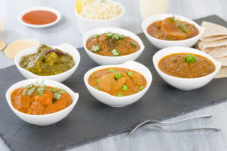 Vegetarian Curries - Selection of South Asian vegetarian curries in white bowls. Paneer Makhani, Palak Paneer, Aloo Matar, Baigan Bharta, Chilli Potatoes and Bhindi Masala. Foto de archivo