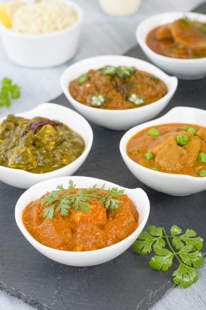 food backgrounds: Vegetarian Curries - Selection of South Asian vegetarian curries in white bowls. Paneer Makhani, Palak Paneer, Aloo Matar, Baigan Bharta, Chilli Potatoes and Bhindi Masala. Stock Photo