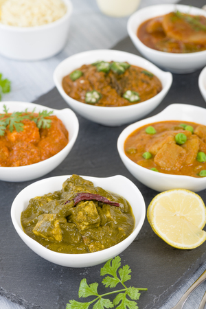 asian food: Vegetarian Curries - Selection of South Asian vegetarian curries in white bowls. Paneer Makhani, Palak Paneer, Aloo Matar, Baigan Bharta, Chilli Potatoes and Bhindi Masala. Stock Photo